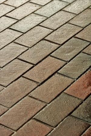 Vertical shot of a wet brick sidewalk after a rain.