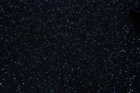 Sparkling dark blue glitter background.