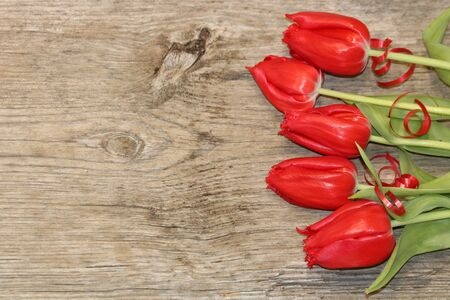 Bright red tulips framing a light brown wood grain background with copy space.