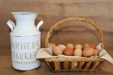 Farm fresh brown eggs in a basket setting beside a white milk jug, all on a burlap background. Stock Photo