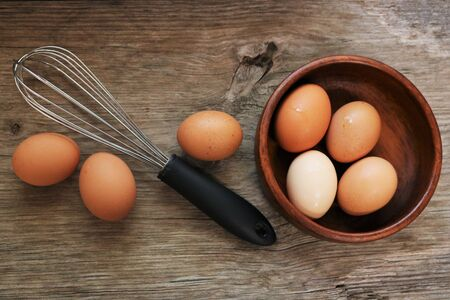 Top view of seven farm fresh brown eggs, four in a wood bowl, three lying beside a wish, on a wooden table. Stock Photo