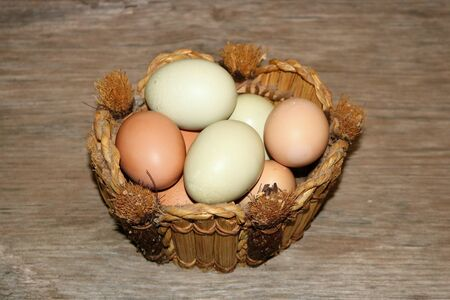 Side view of farm fresh brown and green eggs in a round basket, setting on a wood table. Stock Photo