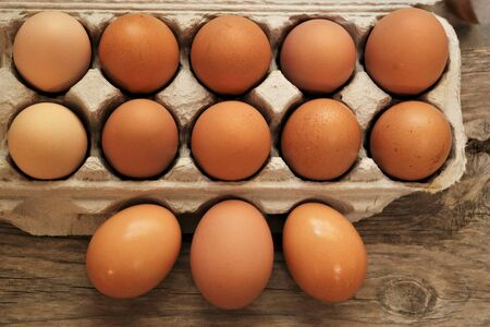 Top view of farm fresh brown eggs in a carton, on a wood table.