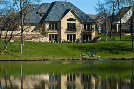 man made: Luxury home on the golf course with man made lake Stock Photo