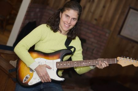 stratocaster: Middle aged woman electric guitar player Stock Photo