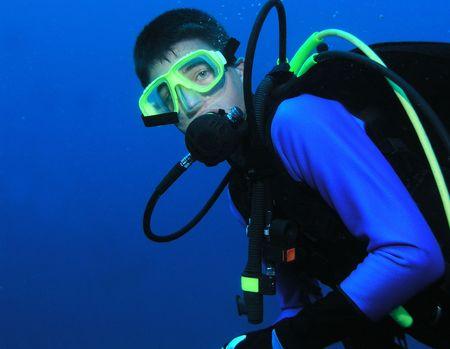 Junge männliche Scuba Diver in Tiefe mit vollständigen Fanggerät auf