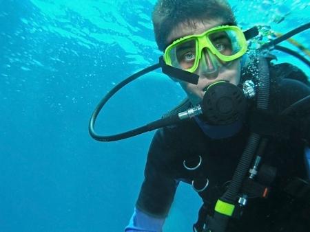 picada: Un joven macho scuba buzo bajo el agua en plena marcha