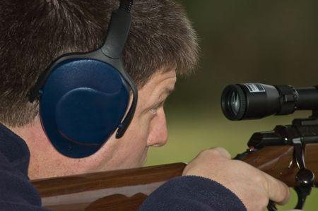 hombre disparando: Hombre disparando una escopeta Foto de archivo