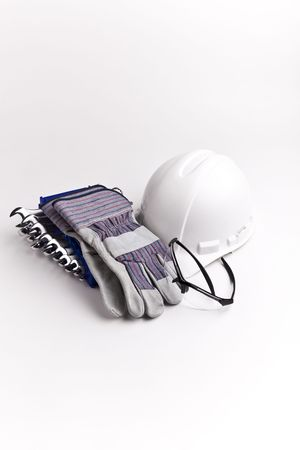 safety: vertical centered  hard hat leather gloves safety glasses wrenches