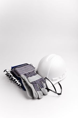 lower section: vertical lower section hard hat leather gloves safety glasses wrenches Stock Photo