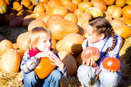 Cute Young Brother and Sister Children sitting on straw with pumkins on farm market. Family celebrating thanksgiving or halloween Stock Photo