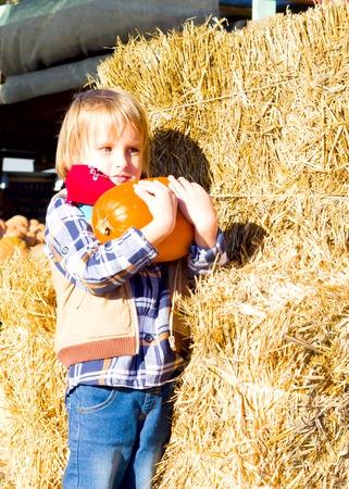 Happy kid boy with pumkins on farm market. Family celebrating thanksgiving or halloween.