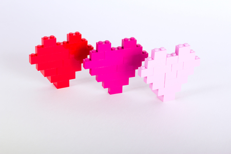 The bricks of the plastic constructor in the form of hearts are red, magenta, pink. White background