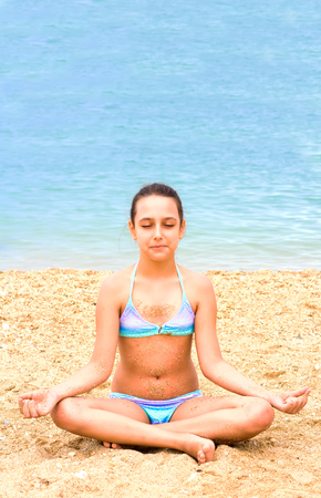 beautiful young teenager girl practice yoga meditation summer sea beach Standard-Bild