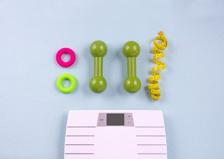 Flat lay composition with sport items, scales on blue background. Weight loss concept. Top view Reklamní fotografie