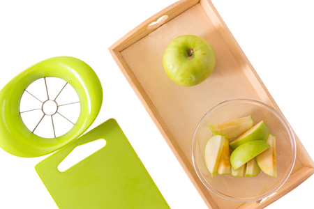 A wooden tray with montessori materials for a lesson from the practical life zone. Apple slicer, cutting board,green apple. Isolate on white background. Flat lay