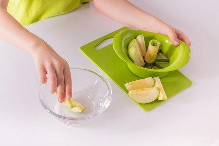 Children's hands are putting sliced apple into a bowl