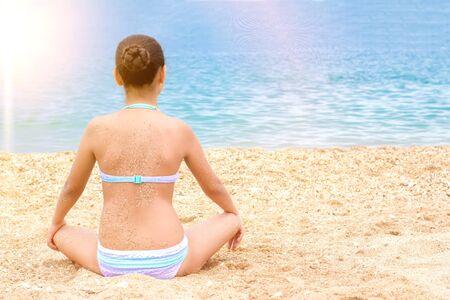 beautiful young teenager girl practice yoga meditation summer sea beach.