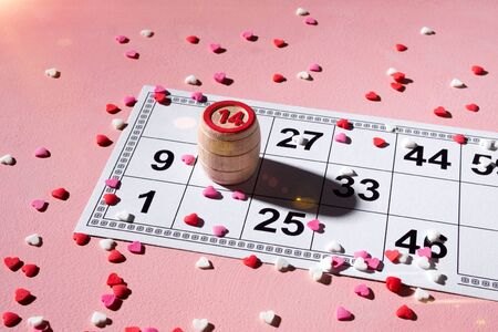 Lotto ticket with wood barrel 14 number on pink hearts background. Valentines day 14 february minimal concept.