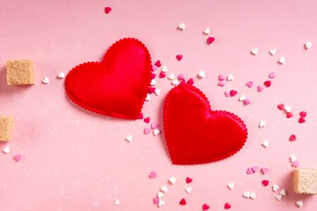 Red fabric hearts, sugar cubes, confetti on pink background. Valentines day 14 february love minimal concept