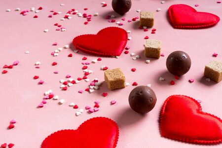 Red fabric hearts, sugar cubes, confetti, sweets candy chocolate on pink background. Valentines day 14 february love concept Archivio Fotografico