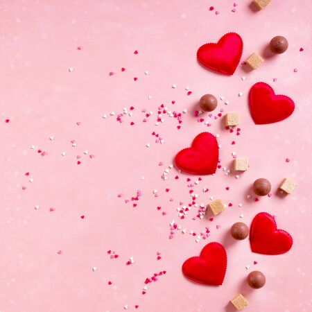 Red fabric hearts, sugar cubes, confetti, sweets candy chocolate on pink background. Valentines day 14 february love minimal concept. Flat lay, copy space, space for text, square banner Archivio Fotografico