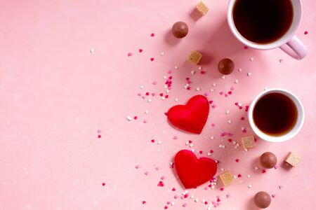 Love drinks. Coffee tea cups, sweets candy chocolate on pink hearts background. Valentines day 14 february minimal concept. Flat lay, above, top view. bokeh effect.