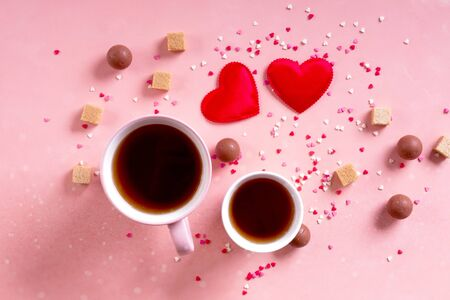 Love drinks. Coffee tea cups for lovers, sweets candy chocolate on pink hearts background. Valentines day 14 february minimal concept. Flat lay, above, top view. bokeh effect.