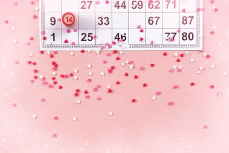 Lotto ticket with wood barrel 14 number on pink hearts background. Valentines day 14 february minimal concept. bokeh effect