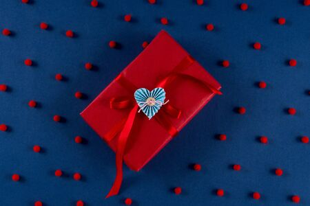 Red gift box with love present and red pompom dots on trend classic blue 2020 color background. Valentines day 14 february concept. Foto de archivo