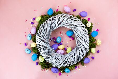 Top view shot of arrangement decoration Happy Easter holiday background concept. Flat lay wreath of twigs and colorful bunny eggs on beautiful pink desk.