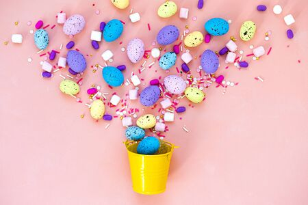 Top view shot of arrangement decoration Happy Easter holiday background concept. Flat lay colorful bunny eggs in a yellow bucket on pink desk. Egg hunt. 免版税图像