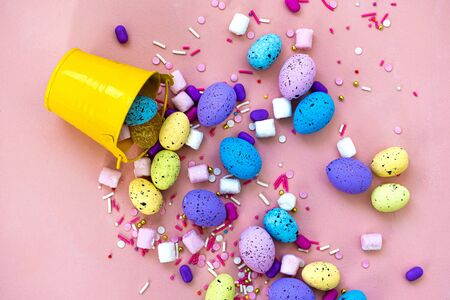 Decoration Happy Easter holiday background concept. Colorful bunny eggs in a yellow bucket on pink desk. Egg hunt.