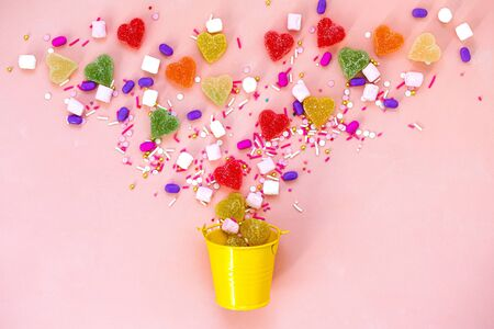 Top view decoration assorted gummy candies and jelly sweets happy holiday background concept. Flat lay colorful candy on beautiful pink desk. Copy space.