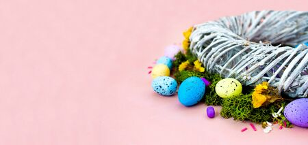 Top view shot of arrangement decoration Happy Easter holiday background concept. Flat lay wreath of twigs and colorful bunny eggs on beautiful pink desk. Wide banner. Copy space