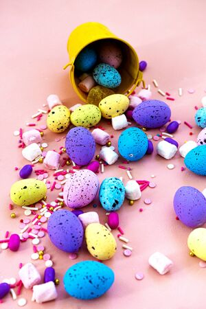 Decoration Happy Easter holiday background concept. Colorful bunny eggs in a yellow bucket on pink desk. Egg hunt 免版税图像