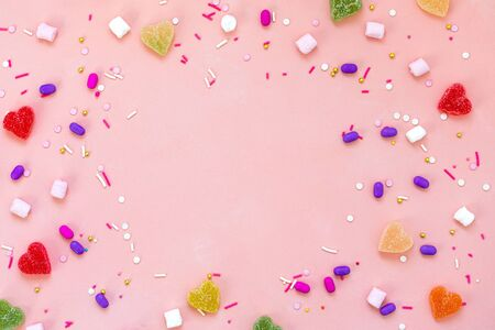 Top view decoration assorted gummy candies and jelly sweets happy holiday background concept. Flat lay colorful candy on beautiful pink desk. Copy space