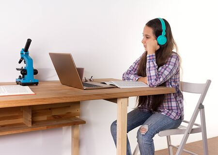 Distance learning.Home schooling, young teen girl studying at a laptop, listening to music with headphones, watching a webinar online, doing science and biology. Elearning concept.