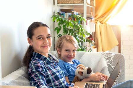 Children study remotely from home sits on the couch.