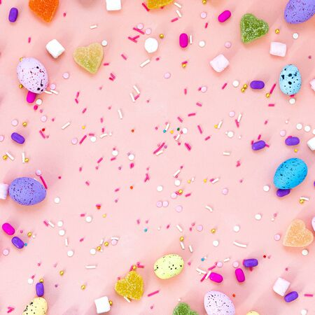 Top view shot of arrangement decoration Happy Easter holiday background concept. Flat lay colorful bunny eggs on beautiful pink desk. Square format. Copy space 免版税图像