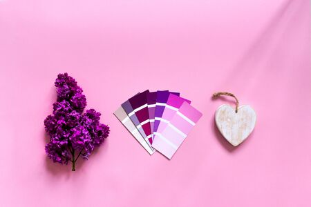 DIY minimalist design concept. Trendy color samples - pink, purple, magenta, lilac flower and white wood rustic heart on pink background. Top view