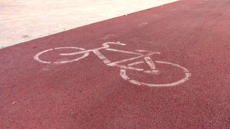 White painted sign for bikes on red bike path