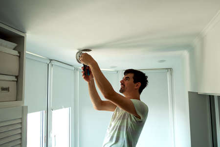 House master male electrician repairs ceiling light indoor home in white room Reklamní fotografie