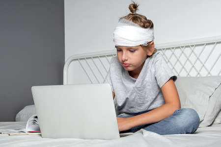 Little Caucasian blond boy with a head injury and bandage is sitting on the bed and using laptop. Recovery after incident. Remote communication, distance learning, technologies and gadgets in life Reklamní fotografie