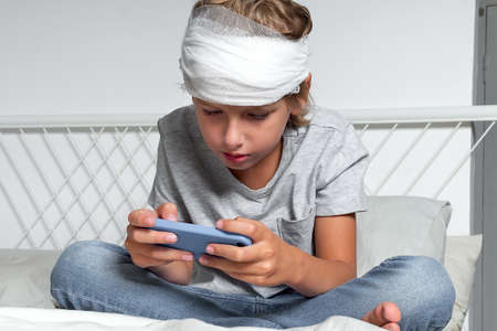 Little Caucasian blond boy with a head injury and bandage is sitting on the bed and using mobile phone. Recovery after incident. Remote communication, technologies and gadgets in life