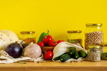 Zero waste bio food storage and shopping concept - groceries in textile bags,glass jars, wooden bowl. Eco friendly plastic free low waste lifestyle. Copy space yellow background.