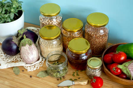 Zero waste healthy food-cereals, seeds, vegetables flat lay on grey background. Groceries in textile bags,glass jars, wooden bowl. Eco friendly plastic free low waste lifestyle.