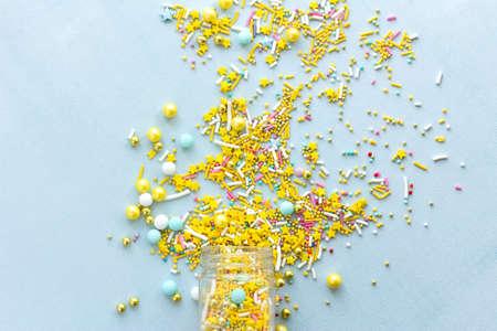 Yellow sugar sprinkles grainy on blue background, close-up flat lay Reklamní fotografie