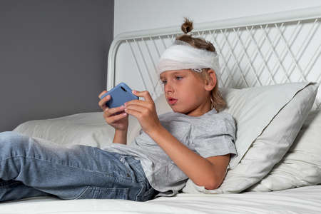 Little Caucasian blond boy with a head injury and bandage is lying on the bed and using mobile phone. Recovery after incident. Remote communication, technologies and gadgets in life