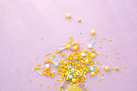 Yellow sugar sprinkles grainy on pink background, close-up flat lay